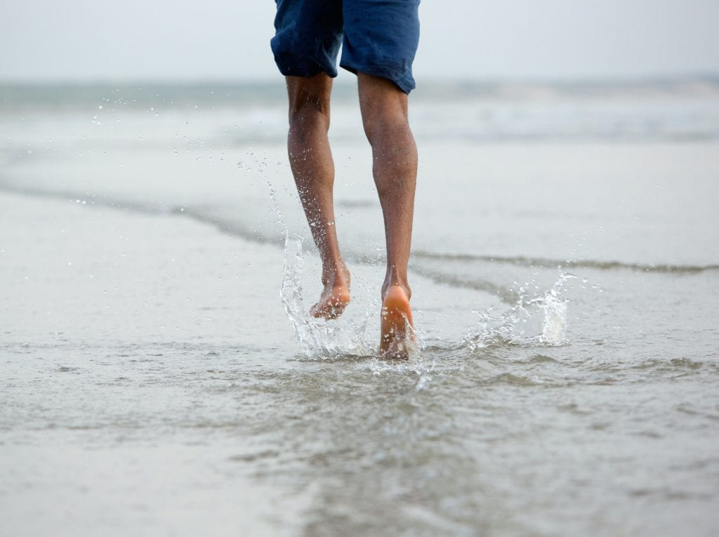 Running with bare feet in water by the beach